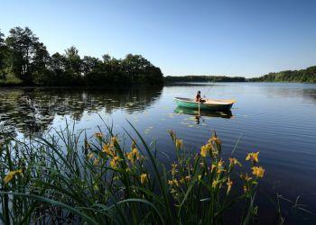 Der Manhagener See mit einem Angler mit Hut.